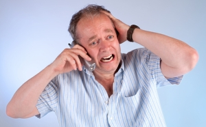 A middle aged man is upset upon receiving very bad news on the telephone.